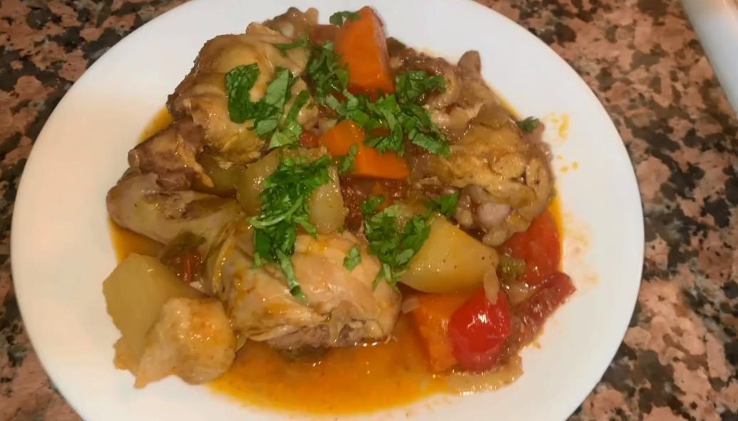 Чахохбили из курицы в казане на плите картошкой и овощами